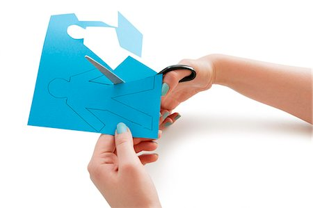 Woman's hand cutting a paper stick figure over white background Stock Photo - Premium Royalty-Free, Code: 693-06324342