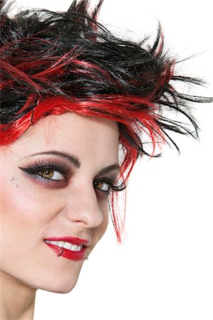 Close-up of beautiful punk woman smiling over white background Stock Photo - Premium Royalty-Free, Code: 693-06324398