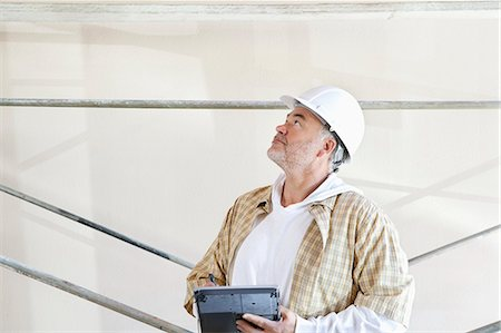 front - Mature male architect making a note in digital tablet while looking up at construction site Stock Photo - Premium Royalty-Free, Code: 693-06324503