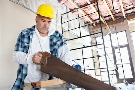 Serious male construction worker cutting wood with handsaw Stock Photo - Premium Royalty-Free, Code: 693-06324517