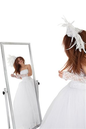 Brunette in wedding gown looking at mirror over white background Stock Photo - Premium Royalty-Free, Code: 693-06324555
