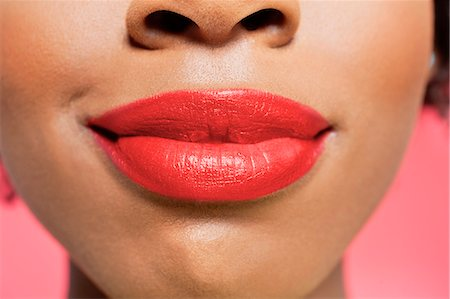 Close-up view of an African American woman's red lips over colored background Stock Photo - Premium Royalty-Free, Code: 693-06324634