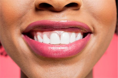 Close-up detail of an African American woman smiling over colored background Stock Photo - Premium Royalty-Free, Code: 693-06324635