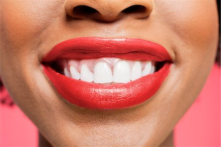 Close-up detail of an African American woman smiling over colored background Stock Photo - Premium Royalty-Free, Code: 693-06324636