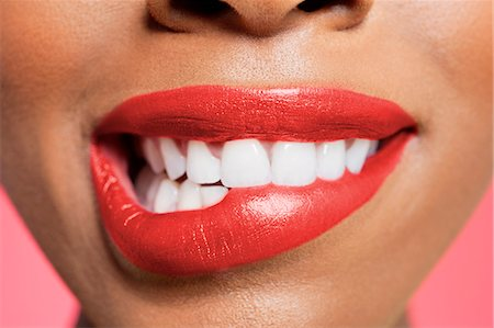 Close-up view of an female biting her red lip over colored background Stock Photo - Premium Royalty-Free, Code: 693-06324638