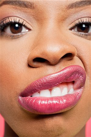 Close-up portrait of young woman with pink lips grimacing Stock Photo - Premium Royalty-Free, Code: 693-06324645
