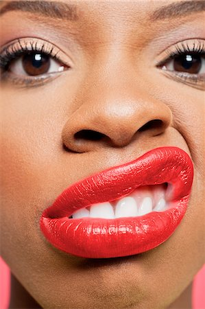 Close-up portrait of young woman with red lips grimacing Stock Photo - Premium Royalty-Free, Code: 693-06324646