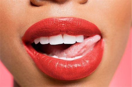 Cropped image of woman licking red lipstick Stock Photo - Premium Royalty-Free, Code: 693-06324640