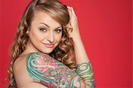female nude hip - Portrait of beautiful young tattooed woman over colored background Stock Photo - Premium Royalty-Free, Code: 693-06324650