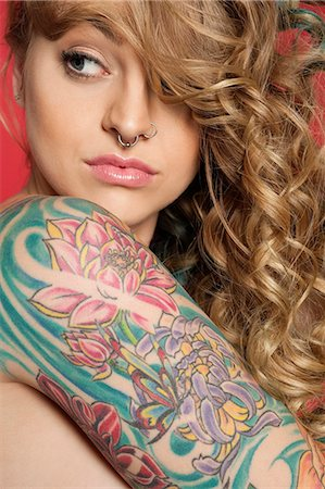 female nude hip - Beautiful young woman looking sideways with tattooed arm Stock Photo - Premium Royalty-Free, Code: 693-06324651