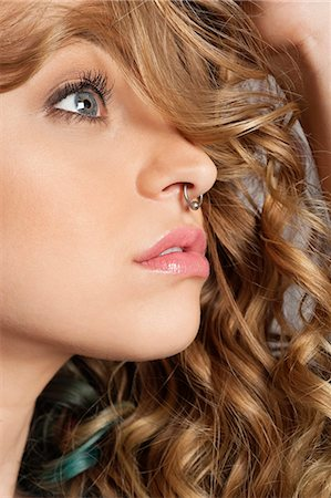 Close-up of beautiful blond woman with pierced nose looking away Stock Photo - Premium Royalty-Free, Code: 693-06324652