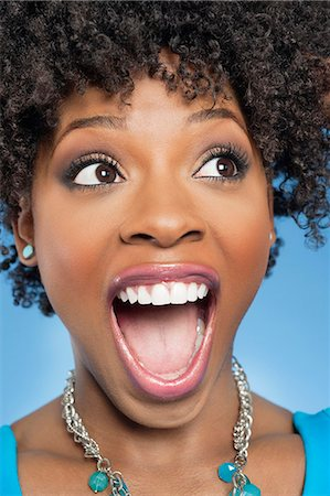 Surprised African American woman looking away with mouth open Stock Photo - Premium Royalty-Free, Code: 693-06324691