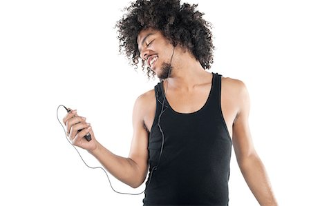 Happy young man listening to mp3 player over white background Foto de stock - Sin royalties Premium, Código: 693-06324714
