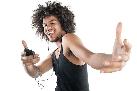 Portrait of a happy young man in vest dancing to tunes of mp3 player over white background Stock Photo - Premium Royalty-Free, Image code: 693-06324715