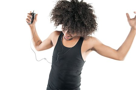 Young man with curly hair enjoying while listening to mp3 player over white background Stock Photo - Premium Royalty-Free, Code: 693-06324716