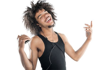 Portrait of a happy young man gesturing while listening to mp3 player over white background Stock Photo - Premium Royalty-Free, Code: 693-06324719