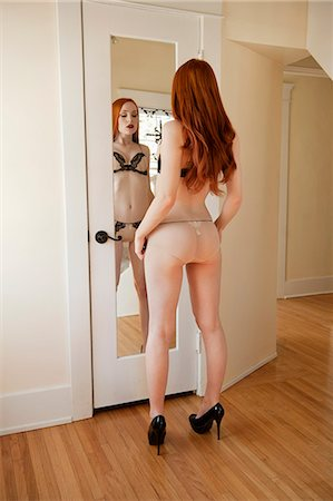 Back view of a young woman in lingerie standing in front of mirror Stock Photo - Premium Royalty-Free, Code: 693-06324743