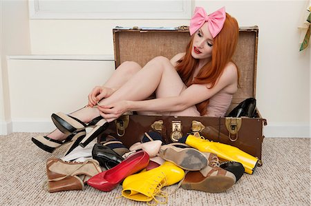 Young woman with bow headband tying footwear while sitting in suitcase Stock Photo - Premium Royalty-Free, Code: 693-06324769