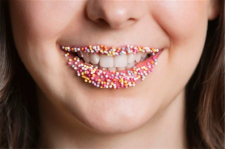 Cropped portrait of Middle Eastern woman with sprinkle candy lips Stock Photo - Premium Royalty-Free, Code: 693-06324775