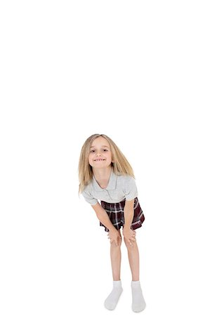Portrait of happy school girl bending over white background Stock Photo - Premium Royalty-Free, Code: 693-06324792