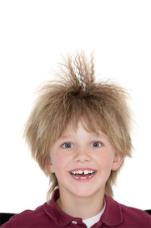 Close-up portrait of a cheerful school boy with spiked hair over colored background Stock Photo - Premium Royalty-Free, Code: 693-06324820