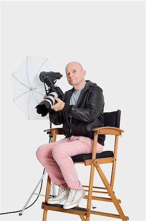 Portrait of senior photographer sitting on director's chair with camera Stock Photo - Premium Royalty-Free, Code: 693-06324855