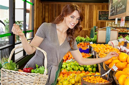 selecting - Portrait of a happy young female shopping for fruits in market Stock Photo - Premium Royalty-Free, Code: 693-06324907