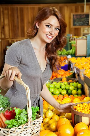 selecting - Portrait of a happy young woman shopping in market for fruits Stock Photo - Premium Royalty-Free, Code: 693-06324909
