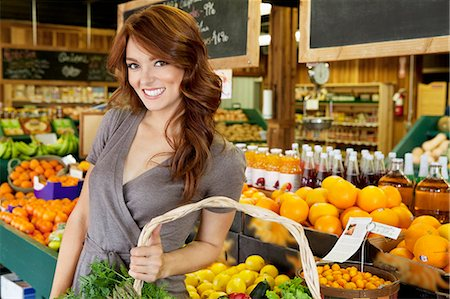 selecting - Portrait of a happy brunette woman standing with basket in fruit market Stock Photo - Premium Royalty-Free, Code: 693-06324910