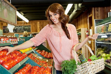 selecting - Portrait of a happy brunette shopping for tomatoes in supermarket Stock Photo - Premium Royalty-Free, Code: 693-06324935
