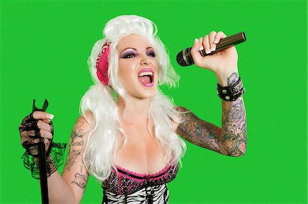 Beautiful tattooed woman singing with microphone over green background Stock Photo - Premium Royalty-Free, Code: 693-06324969