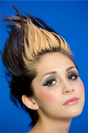 Close-up portrait of beautiful young woman with spiked hair over blue background Stock Photo - Premium Royalty-Free, Code: 693-06325026