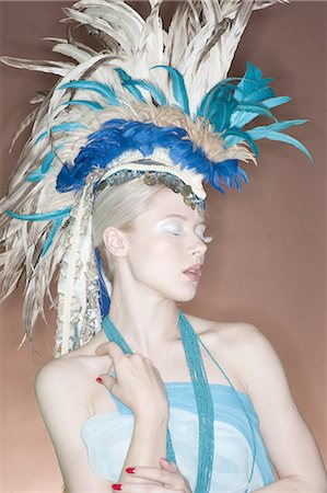 Beautiful young woman wearing feather headgear with eyes closed Stock Photo - Premium Royalty-Free, Code: 693-06325033