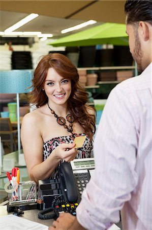 person on phone with credit card - Portrait of a happy young woman paying through credit card in store Stock Photo - Premium Royalty-Free, Code: 693-06325061