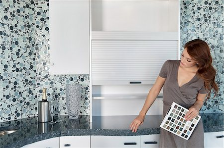 decision - Beautiful young woman with color samples looking at contemporary kitchen cabinets Stock Photo - Premium Royalty-Free, Code: 693-06325093