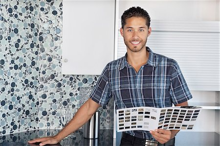 Portrait of young man with color samples standing in model home kitchen Stock Photo - Premium Royalty-Free, Code: 693-06325115