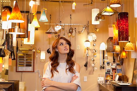 Beautiful young woman browsing for lights with arms crossed in store Stock Photo - Premium Royalty-Free, Code: 693-06325147