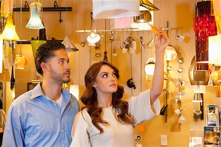 Young couple looking at price tag of lighting equipment in lights store Stock Photo - Premium Royalty-Free, Code: 693-06325148