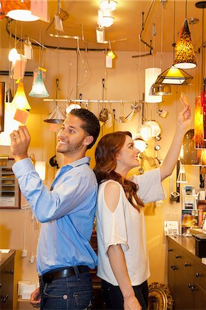 Happy young couple standing back to back while looking at price tag in lights store Stock Photo - Premium Royalty-Free, Code: 693-06325151