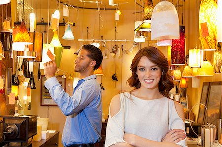 Portrait of young woman with arms crossed while man looking at price tag in background in lights store Stock Photo - Premium Royalty-Free, Code: 693-06325153
