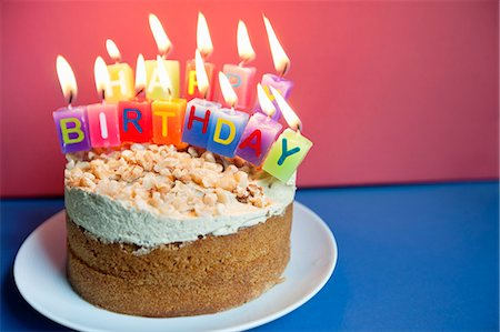 Close-up of candles burning on birthday cake over colored background Stock Photo - Premium Royalty-Free, Code: 693-06325234