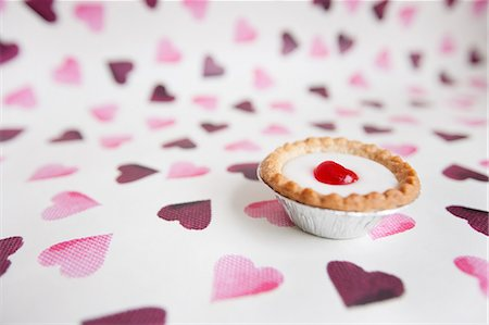 Close-up of cupcake over heart shaped background Stock Photo - Premium Royalty-Free, Code: 693-06325238