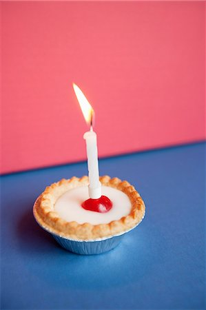 Close-up of candle burning on cupcake over colored background Stock Photo - Premium Royalty-Free, Code: 693-06325232