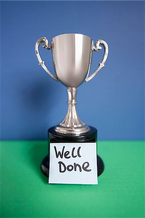 Winning trophy award with sticky note over colored background Stock Photo - Premium Royalty-Free, Code: 693-06325252