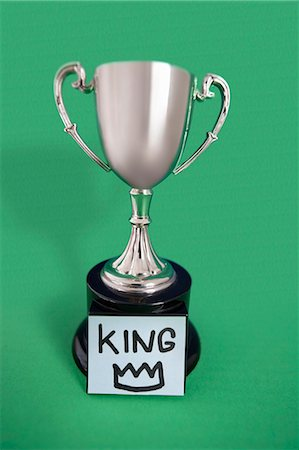Trophy with sticky note over colored background Stock Photo - Premium Royalty-Free, Code: 693-06325253