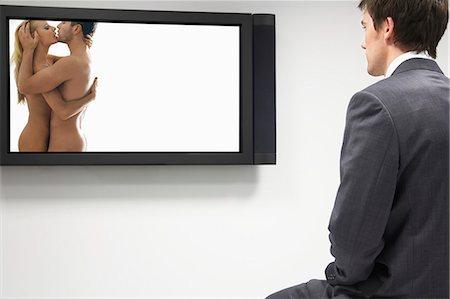 Businessman watching erotic naked couple on flat screen Stock Photo - Premium Royalty-Free, Code: 693-06325300