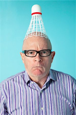 Portrait of angry man with shuttlecock on head over colored background Stock Photo - Premium Royalty-Free, Code: 693-06323938