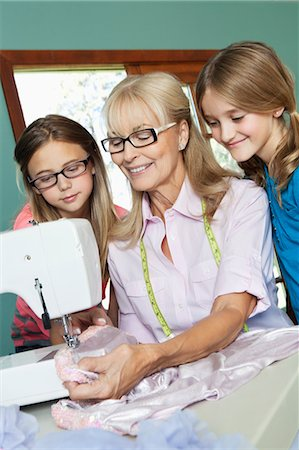 Girls looking grandmother sewing cloth Stock Photo - Premium Royalty-Free, Code: 693-06378763