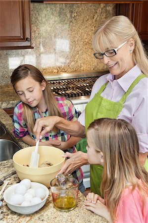 Senior woman with granddaughters mixing batter in kitchen Stock Photo - Premium Royalty-Free, Code: 693-06378774