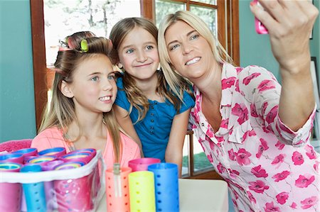 Mother with daughters taking self portrait with cell phone Stock Photo - Premium Royalty-Free, Code: 693-06378770